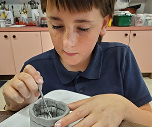 Student working with clay in art class